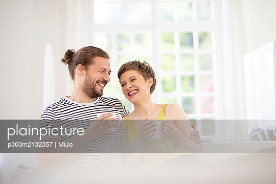 Happy young couple holding cups on couch at home - p300m2132357 von MiJo