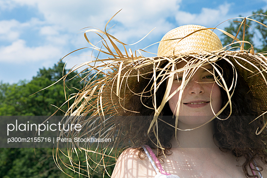 Portrait of smiling young woman wearing frayed straw hat in nature - p300m2155716 by Petra Stockhausen