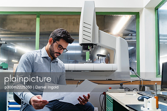 Male entrepreneur reading document while sitting in industry - p300m2225350 by Daniel Ingold