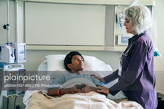 Doctor comforting boy in hospital bed holding cell phone - p555m1521455 by FS Productions