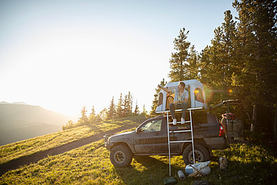 Man taking selfie at SUV rooftop tent in sunny field, Alberta, Canada - p1192m2016505 by Hero Images