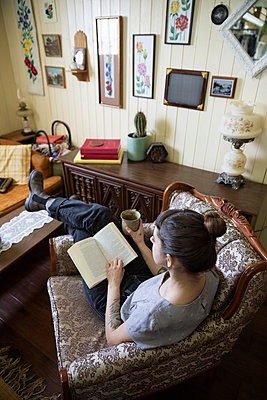 Woman reading book and drinking coffee in living room - p1192m2088178 by Hero Images