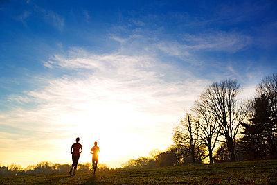 Zwei Jogger im Sonnenuntergang - p1211m1109066 von Danny Weiss
