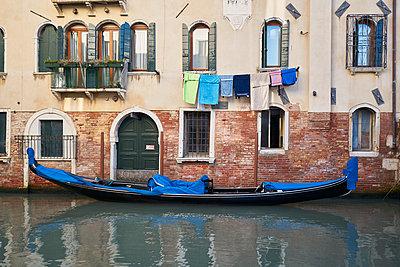 Gondel an einer Hauswand mit Wäscheleine und Wäsche in Venedig  - p1312m2082219 von Axel Killian