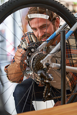 Mechanic repairing bicycle in workshop - p623m2214737 by Frederic Cirou