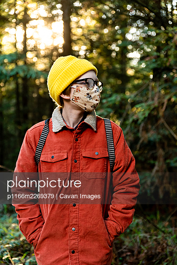 Young person standing in forest wearing mask during global pandemic - p1166m2269379 by Cavan Images