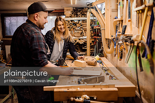 carpenter communicates with woman customer in his workshop - p1166m2279319 by Cavan Images