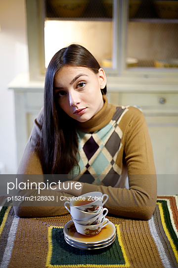 Young woman in retro sweater in front of cups of tea - p1521m2128933 by Charlotte Zobel