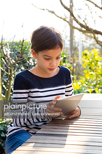 Portrait of little girl sitting at garden table looking at digital tablet - p300m2180369 by Larissa Veronesi