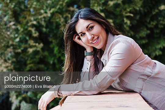 Beautiful woman leaning on retaining wall during sunny day - p300m2274008 by Eva Blanco