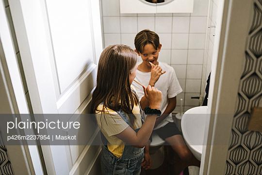 Siblings brushing teeth in bathroom - p426m2237954 by Maskot