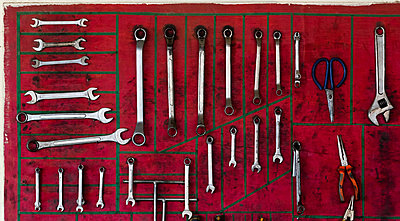 Various wrenches with pliers and scissors arranged on red wall in workshop - p1166m2066031 by Cavan Social