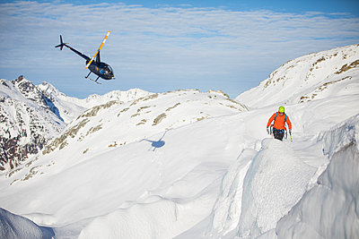 Helicopter approaches mountaineer in a mountain landscape. - p1166m2124321 by Cavan Images