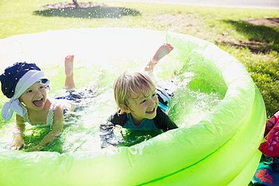 Playful brother and sister in wading pool in sunny backyard - p1192m1184000 by Hero Images