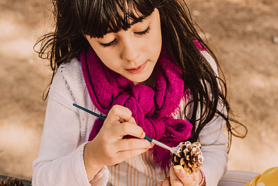 Cute girl coloring pine cone with paintbrush at park - p300m2225828 by Eloisa Ramos