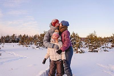 Kissing parents embracing cute daughter in snow during winter - p300m2265148 by Ekaterina Yakunina
