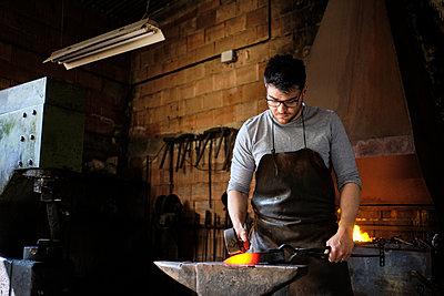 Craftsman hitting overheated metal on anvil at workshop - p300m2281459 by Antonio Ovejero Diaz