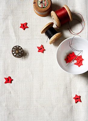 Red star shaped buttons with spools of thread on linen tablecloth;  Isle of Wight home;  UK - p349m920062 by Rachel Whiting