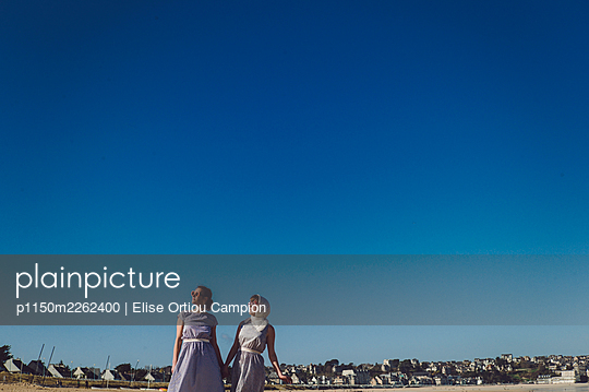 Two women in summer dresses - p1150m2262400 by Elise Ortiou Campion