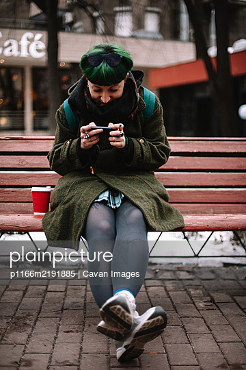 Portrait of happy non-binary hipster using smart phone in city - p1166m2191885 by Cavan Images