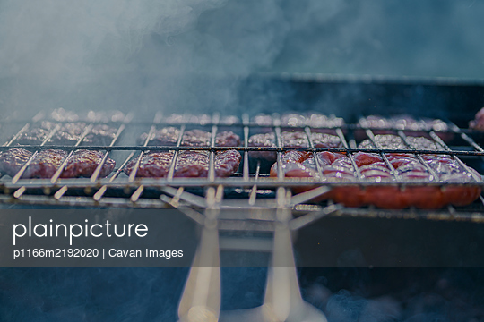 preparation of barbecue on bacon and sausage grill - p1166m2192020 by Cavan Images