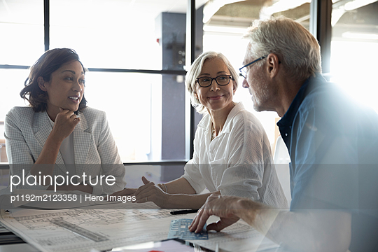 Clients discussing plans with design professional in studio - p1192m2123358 by Hero Images