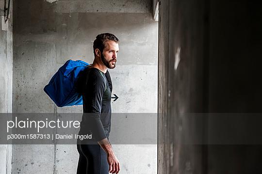 Athlete holding bag at concrete wall - p300m1587313 von Daniel Ingold
