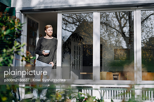 Man in sunroom at home leaning against the window - p300m2166637 by Kniel Synnatzschke