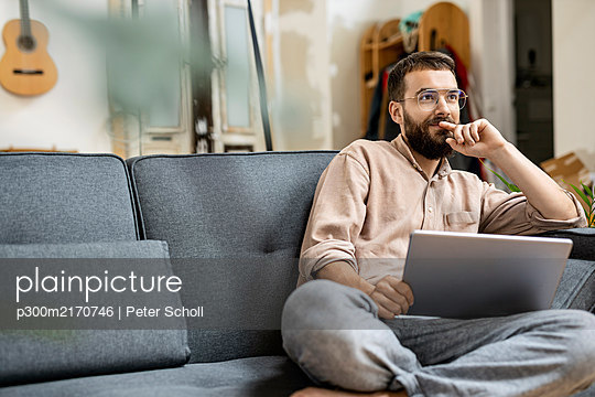 Young man sitting at home on couch, using digital tablet - p300m2170746 by Peter Scholl