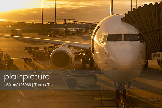Commercial airplane parked at terminal on tarmac at sunset - p301m2123066 by Tobias Titz