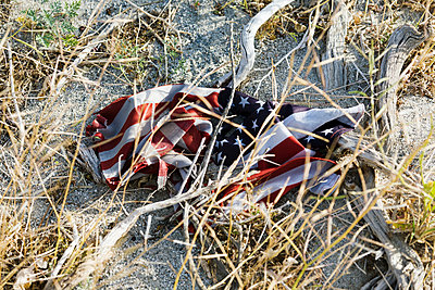 An American flag, crumpled up on the sandy ground, damaged,  - p1100m2090772 by Mint Images