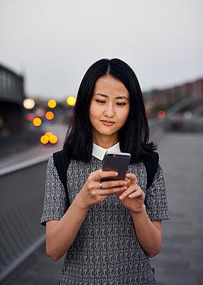 Junge Asiatin mit Smartphone  - p1124m1169917 von Willing-Holtz