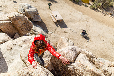 High angle view of hiker climbing rocks at Joshua Tree National Park during sunny day - p1166m1414736 by Cavan Images