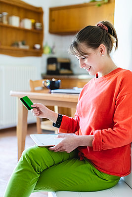 Woman with credit card doing home shopping through digital tablet at home - p300m2282355 by 27exp