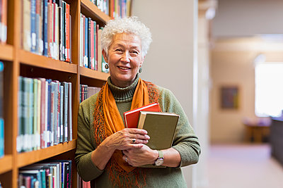 Older mixed race woman holding books in library - p555m1306140 by Marc Romanelli