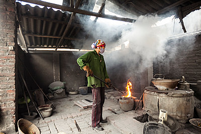A female Vietnamese worker in Man Xa Village holds a tool to an open flame as smoke billows through the roof, northern outskirts of Hanoi, Vietnam, Southeast Asia.  - p934m1093539f by Aaron Joel Santos