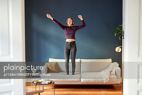 Junge Frau mit Kopfhörern tanzt auf dem Sofa - p1124m1589222 von Willing-Holtz