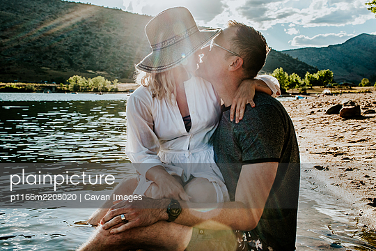 husband and wife sitting together and kissing on lakeshore - p1166m2208020 by Cavan Images
