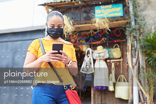 Young woman with  wearing masks outside a local craft market - p1166m2268882 by Cavan Images