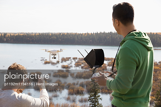 Male friends with drone equipment and camera phone overlooking lake - p1192m1194116 by Hero Images