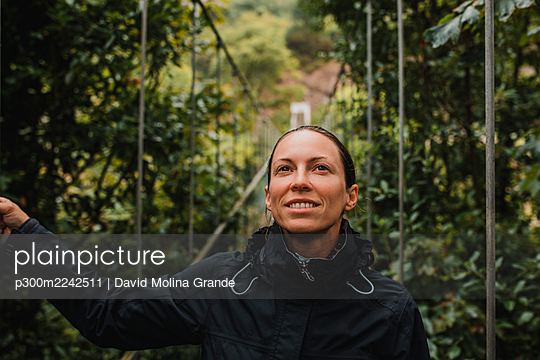 Thoughtful woman wearing raincoat standing on suspension bridge in forest - p300m2242511 by David Molina Grande