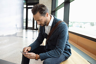 Businessman using smart phone in lobby - p1192m2047537 by Hero Images