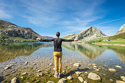Spain, Asturias, Picos de Europa National Park, man standing with raised arms at Lakes of Covadonga - p300m1449430 by Maria Elena Pueyo Ruiz