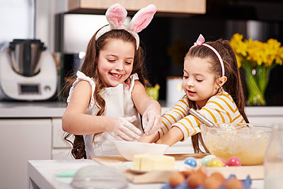 Two sisters having fun baking Easter cookies in kitchen together - p300m1567651 by gpointstudio