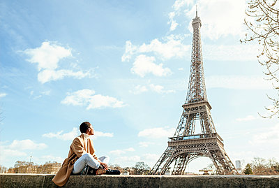 Young woman looking at Eiffel Tower against sky during sunny day in Paris, France - p300m2199173 by Kiko Jimenez