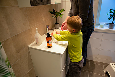 Father and son washing hands in bathroom - p312m2190952 by Madeleine Wejlerud