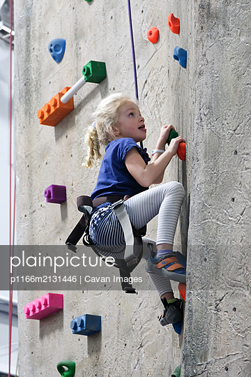 young girl climbing rock wall at indoor rock climbing gym - p1166m2131446 by Cavan Images