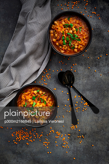 Studio shot of lentil and chickpea soup (red lentils, chickpeas, tomatoes, red onions, mint) - p300m2166845 by Larissa Veronesi