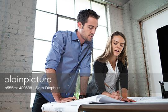 Caucasian architects designing blueprints in office - p555m1420338 by Sam Diephuis