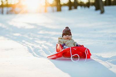 Portrait of cute baby girl sitting in sled on snowy field at park - p1166m1543148 by Cavan Images